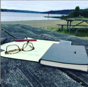 close-up of a notepad, pen and eyeglasses on a weatherbeaten picnic table ona deserrted beach